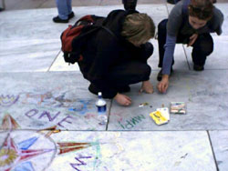 Two activists drawing compass roses on the ground.